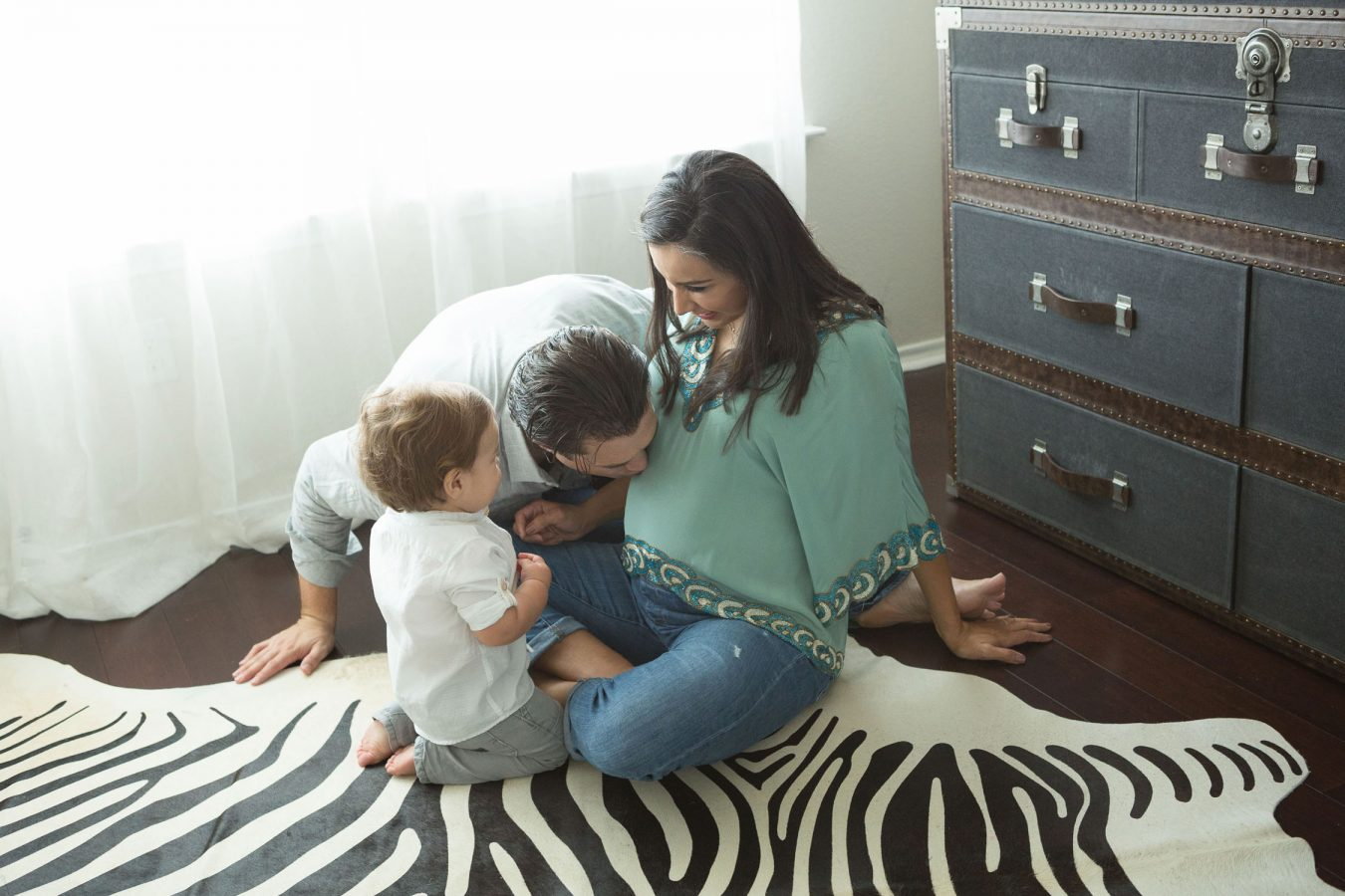 family in nursery of new baby kissing belly at home in San Antonio