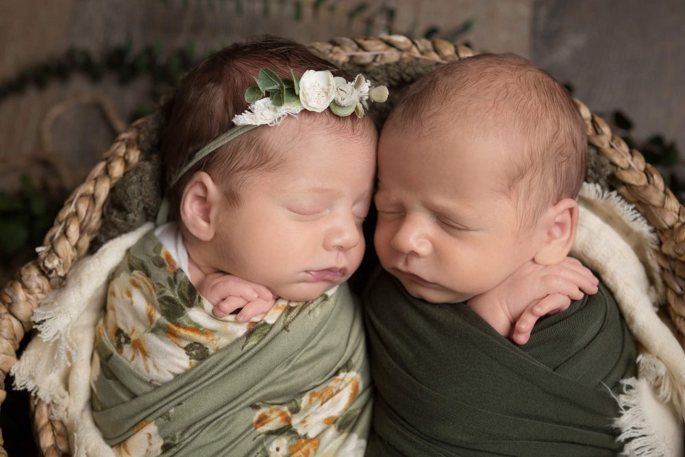 twin newborns wrapped in green during photography session in San Antonio, Texas